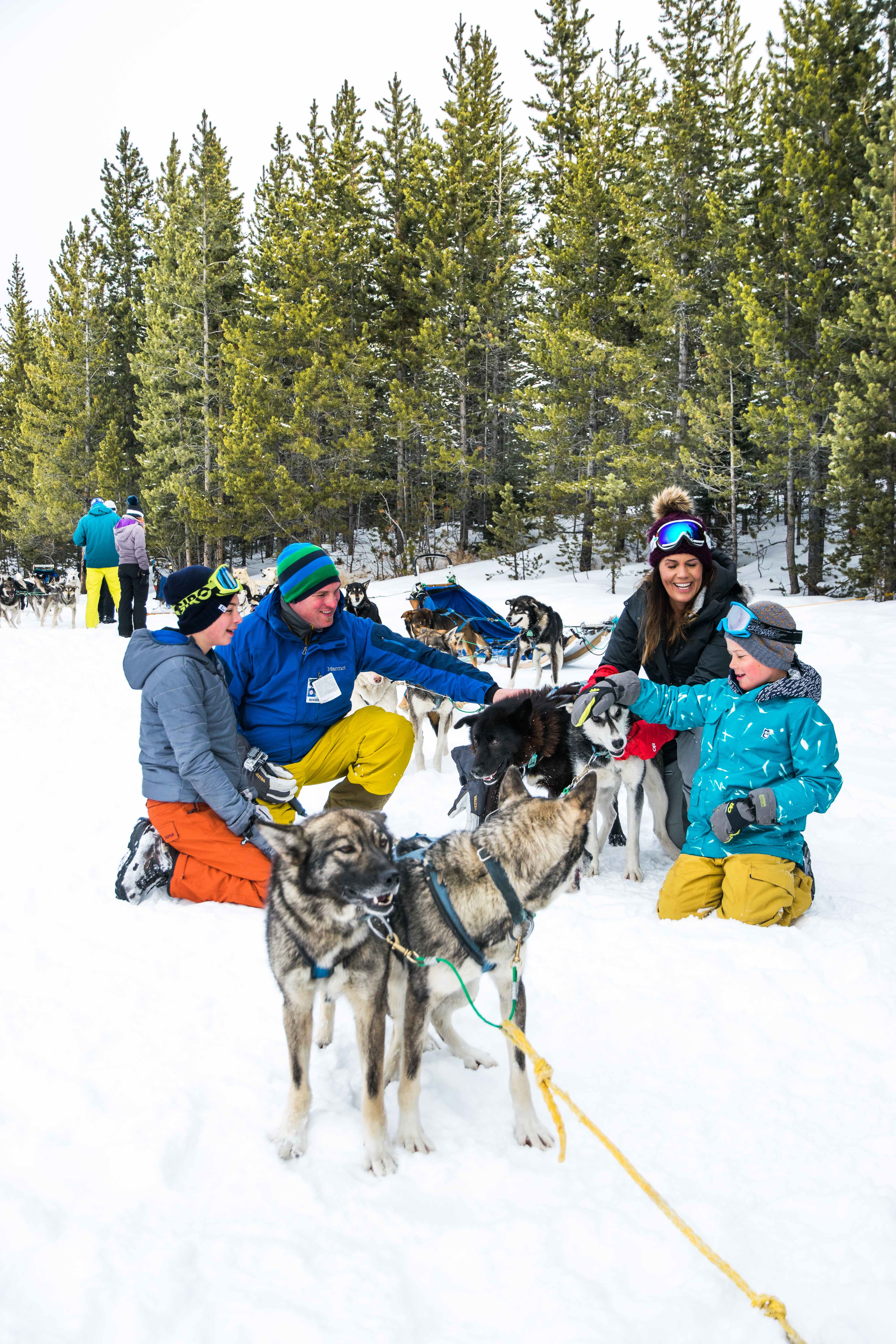 Family takes a break while dog sledding in Montana's Yellowstone Country.